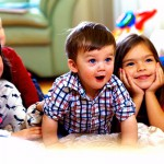 group of happy kids watching tv at home